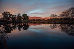 Lago calmo dell'altopiano La riflessione delle montagne e gli alberi ed il cielo di sera di crepuscolo in lago innaffiano Immagine Stock Libera da Diritti
