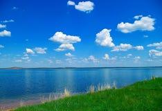 Lago, cielo nuvoloso blu ed erba verde Fotografia Stock