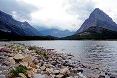 Lago claro y altas montañas en Parque Nacional Glacier Imagen de archivo