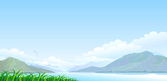 Lago, colinas y cielo azul extenso Imagenes de archivo