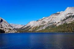 Lago com água clara, cercada por montanhas fotografia de stock