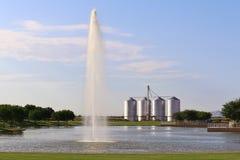 Lago com fonte e silos no fundo Foto de Stock Royalty Free
