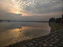 Lago com o nascer do sol que faz a maneira através das nuvens fotografia de stock
