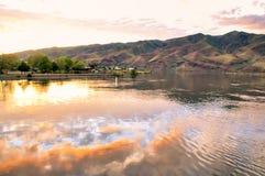 Lago com reflexão do céu do por do sol, e casas e montes no rio Snake da distância na beira de estados de Idaho e de Washington Foto de Stock