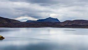 Lago com reflexão pequena da ilha e do céu no dia nebuloso em Islândia Fotografia de Stock Royalty Free