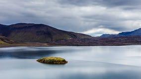 Lago com reflexão pequena da ilha e do céu no dia nebuloso em Islândia Imagem de Stock Royalty Free