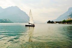 Lago Como em Lecco com o veleiro que navega da cidade fotografia de stock