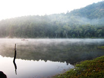 Lago con el bote pequeño en la niebla de la mañana Foto de archivo libre de regalías