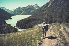 Lago con el canto rocoso Paisaje hermoso El turista pasa las rocas en la orilla del lago Altay Russia imagen de archivo