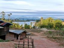 Lago con las pequeñas chozas y el paisaje lateral de la colina Fotos de archivo libres de regalías