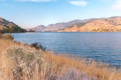 Lago con le erbe di autunno in priorità alta e le montagne nel fondo con cielo blu Fotografia Stock