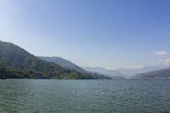 Lago con los barcos en el fondo de un valle verde de la montaña debajo del cielo azul, visión Phewa desde el agua fotos de archivo
