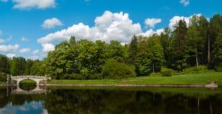 Lago con un puente de piedra en el parque de la ciudad Fotos de archivo libres de regalías