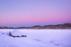 Lago congelado com neve durante o por do sol da noite em Noruega imagens de stock