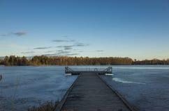 Lago congelado com a ponte do gelo e da madeira na Suécia na noite da mola Imagens de Stock Royalty Free
