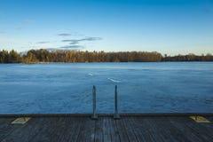 Lago congelado com a ponte do gelo e da madeira na Suécia na noite da mola Foto de Stock