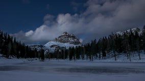 Lago congelado de la montaña y montañas alpinas iluminados por el moonlig Foto de archivo