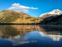 Lago congelato con la riflessione delle montagne nelle alpi svizzere Immagine Stock