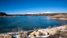 Lago congelato e montagne innevate fotografia stock libera da diritti