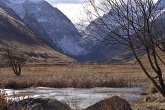 Lago congelato in un freddo della valle della montagna in autunno immagine stock