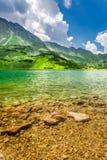 Lago cristalino en el medio de las montañas Foto de archivo