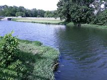 Lago de enrrollamiento rodeado por la naturaleza pacífica fotos de archivo