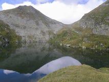 Lago de la montaña de la mucha altitud, rodeado por las piedras grandes Foto de archivo