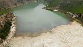 Lago de turquesa da montanha da vista aérea entre os montes no tempo e na névoa nebulosos do dia Paisagens do Cáucaso norte video estoque