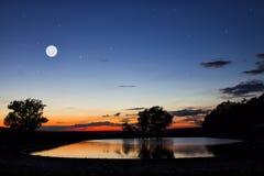 Lago del bosque en las montañas en la puesta del sol Fotografía de archivo