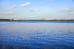 Lago del color azul brillante, del cielo y del bosque en la costa costa Fotos de archivo libres de regalías