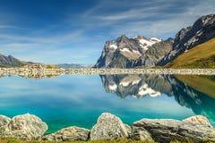 Lago del turchese e alte montagne alpini, Bernese Oberland, Svizzera Fotografia Stock
