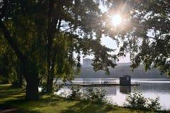 Lago dell'allume di jezero di Kamencove in città ceca di Chomutov con due genti che riposano sul molo che conduce al posto di soc Fotografia Stock Libera da Diritti