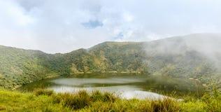 Lago dentro da cratera do vulcão de Bisoke, parque nacional do vulcão de Virunga foto de stock