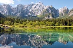 Lago di Fusine e riflesso di Mangart del monte sul lago Fotografie Stock