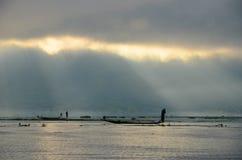 LAGO DI INLE, MYANMAR 20 SETTEMBRE 2016: Siluette di pesca locale del pescatore per l'alimento ad alba Fotografia Stock