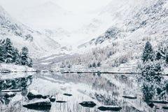 Lago di inverno della montagna con la riflessione delle rocce nella superficie dell'acqua Fotografia Stock