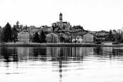 Lago di Pusiano. A small town mirrored by the lake's water Black and white cityscape royalty free stock photography