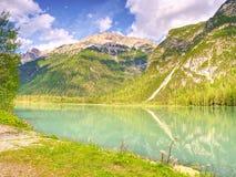 Lago di verde blu fra le montagne rocciose taglienti Superficie regolare dell'acqua, Fotografie Stock Libere da Diritti