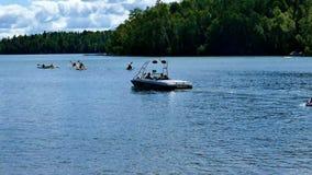 Lago do norte bonito Minnesota com os paddlers e o barco da velocidade que puxam tubérculos vídeos de arquivo