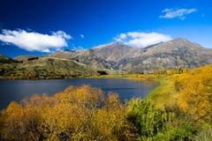 Lago e céu azuis, montanhas, cercadas por árvores amarelas, alaranjadas e verdes fotografia de stock