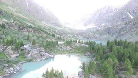 Lago e cascata del turchese di Kuyguk in montagne di Altai Vista aerea russa del paesaggio archivi video