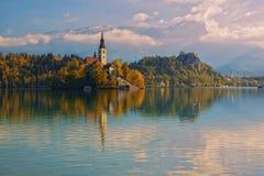 Lago e chiesa sanguinati di pellegrinaggio con il fondo del paesaggio della montagna di autunno Immagini Stock