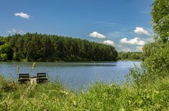 Lago e floresta bonitos no fundo, no céu azul e nas nuvens brancas fotografia de stock