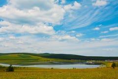 Lago e grama verde sob o céu azul e as nuvens brancas fotografia de stock royalty free