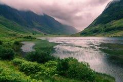 Lago e montanhas com nuvens dramáticas, Escócia Foto de Stock Royalty Free