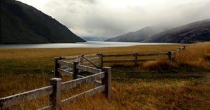 Lago e montanhas e exploração agrícola nevoentos com grama murcho e cerca do ziguezague Imagens de Stock