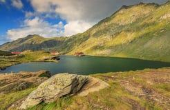 Lago e restaurante alpinos em um lago, lago Balea, montanhas de Fagaras, Carpathians, Romênia Fotografia de Stock