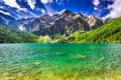 Lago en el medio de las montañas en el amanecer Fotos de archivo