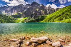 Lago en el medio de las montañas en la salida del sol Imagenes de archivo