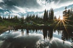 Lago en la cumbre de la reflexión de la puesta del sol de Revelstoke del soporte sunstar a través de bosque con el cielo azul y l Imagenes de archivo